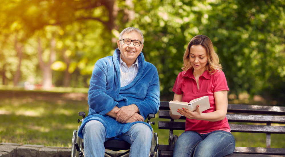 caregiver reading some books to elderly patient
