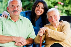 caregiver hugging two elderly patient