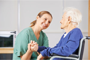 caregiver holding the hands of elderly patien in a wheelchair